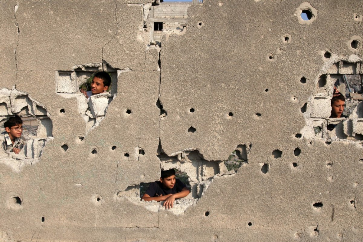 palestinian children look out of their familys house.jpg